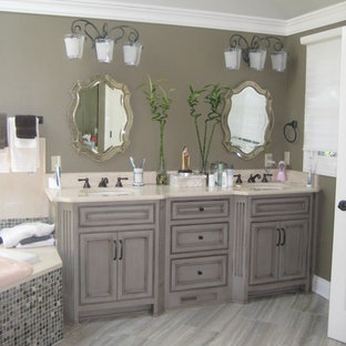 Inspiration for a mid-sized shabby-chic style master beige tile and stone slab porcelain floor and brown floor bathroom remodel in Cleveland with beaded inset cabinets, gray cabinets, solid surface countertops, a hinged shower door, a two-piece toilet, brown walls and an undermount sink