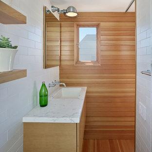 Ejemplo de cuarto de baño principal, contemporáneo, de tamaño medio, con lavabo bajoencimera, armarios con paneles lisos, puertas de armario de madera oscura, encimera de piedra caliza, baldosas y/o azulejos blancos, baldosas y/o azulejos de cemento y suelo de madera en tonos medios