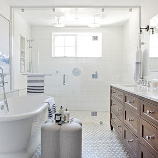 Inspiration for a traditional ensuite bathroom in Cambridgeshire with recessed-panel cabinets, dark wood cabinets, a freestanding bath, a built-in shower, white tiles, white walls, mosaic tile flooring, a submerged sink, white floors, a hinged door and white worktops.