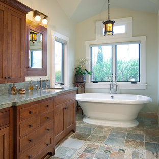 Large arts and crafts master bathroom in San Diego with recessed-panel cabinets, medium wood cabinets, a freestanding tub, beige walls, an undermount sink, granite benchtops, slate floors, gray tile, stone slab, a two-piece toilet and multi-coloured floor.