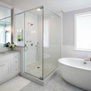 Idéer för ett stort modernt grå en-suite badrum, med luckor med profilerade fronter, vita skåp, ett fristående badkar, en hörndusch, en toalettstol med separat cisternkåpa, grå kakel, tunnelbanekakel, grå väggar, marmorgolv, ett undermonterad handfat, marmorbänkskiva, grått golv och dusch med gångjärnsdörr