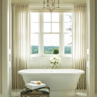 Imagen de cuarto de baño principal, clásico, grande, con bañera exenta, paredes beige, armarios con paneles con relieve, puertas de armario blancas, ducha empotrada, sanitario de dos piezas, suelo de mármol, lavabo bajoencimera y encimera de granito