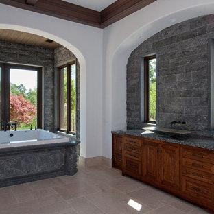 Freestanding bathtub - huge mediterranean master gray tile and stone tile freestanding bathtub idea in Sacramento with a vessel sink, raised-panel cabinets, medium tone wood cabinets, granite countertops and gray walls