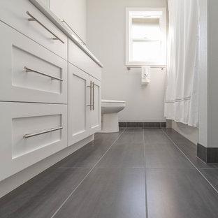 Cette image montre une petite salle de bain minimaliste pour enfant avec un placard à porte plane, des portes de placard en bois clair, une baignoire posée, une douche ouverte, un WC à poser, un carrelage gris, des carreaux de céramique, un mur blanc, un sol en carrelage de céramique, un lavabo encastré, un plan de toilette en quartz modifié et un sol gris.