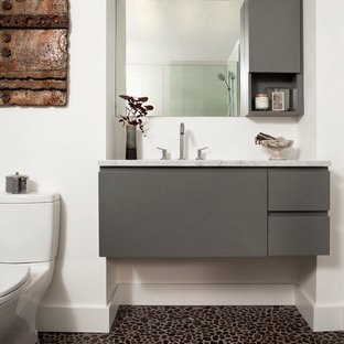 Bathroom - mid-sized contemporary pebble tile floor bathroom idea in Denver with white walls, a one-piece toilet, an undermount sink, flat-panel cabinets, gray cabinets, marble countertops and white countertops