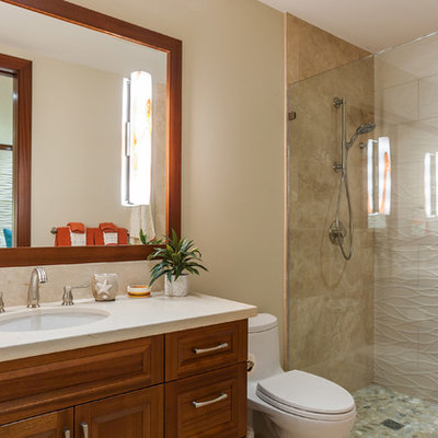 Inspiration for a tropical 3/4 beige tile alcove shower remodel in Hawaii with raised-panel cabinets, medium tone wood cabinets, a one-piece toilet, beige walls, an undermount sink and a hinged shower door