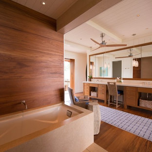 Design ideas for a large world-inspired ensuite bathroom in Hawaii with flat-panel cabinets, medium wood cabinets, a submerged bath, white walls, medium hardwood flooring, an integrated sink, engineered stone worktops, an alcove shower, a two-piece toilet, white tiles, stone slabs, brown floors and a hinged door.