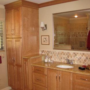 Cette photo montre une salle de bain principale chic de taille moyenne avec un lavabo encastré, un placard avec porte à panneau surélevé, des portes de placard en bois clair, un plan de toilette en granite, un carrelage beige, un carrelage de pierre et un mur beige.