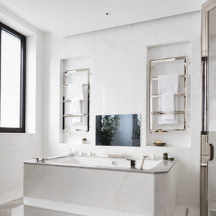 Inspiration for a contemporary bathroom in London with a submerged bath, white tiles and grey floors.