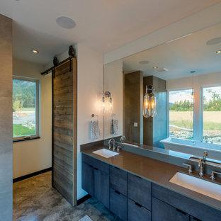 На фото: большая главная ванная комната в стиле рустика с плоскими фасадами, коричневыми фасадами, душем в нише, белой плиткой, керамогранитной плиткой, белыми стенами, бетонным полом, врезной раковиной, столешницей из переработанного стекла, бежевым полом, открытым душем и серой столешницей с