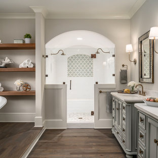 Example of a transitional master dark wood floor and brown floor bathroom design in Charlotte with recessed-panel cabinets, gray cabinets, gray walls, an undermount sink, a hinged shower door and beige countertops