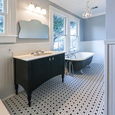 Example of a mid-sized classic 3/4 white tile and subway tile ceramic tile and multicolored floor bathroom design in Houston with furniture-like cabinets, black cabinets, a two-piece toilet, gray walls, an undermount sink, solid surface countertops and a hinged shower door