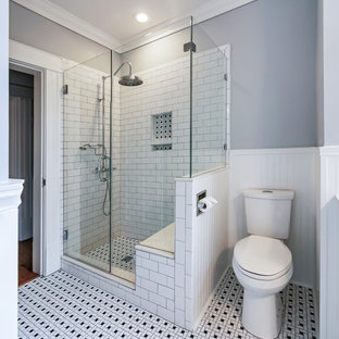Example of a mid-sized classic 3/4 white tile and subway tile multicolored floor and ceramic floor bathroom design in Houston with a two-piece toilet, gray walls, furniture-like cabinets, black cabinets, an undermount sink, solid surface countertops, a hinged shower door and a niche