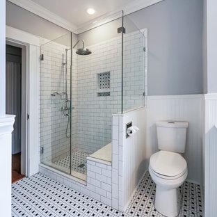 Bild på ett mellanstort vintage badrum med dusch, med en toalettstol med separat cisternkåpa, grå väggar, flerfärgat golv, möbel-liknande, svarta skåp, ett badkar med tassar, en hörndusch, vit kakel, tunnelbanekakel, klinkergolv i keramik, ett undermonterad handfat, bänkskiva i akrylsten och dusch med gångjärnsdörr