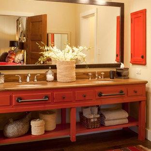 Inredning av ett rustikt brun brunt badrum, med träbänkskiva, röda skåp, mörkt trägolv och ett undermonterad handfat