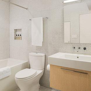Foto di una stanza da bagno minimalista con lavabo a consolle, ante lisce, ante in legno chiaro, vasca ad alcova, vasca/doccia, WC a due pezzi, piastrelle bianche, piastrelle a mosaico e pavimento con piastrelle a mosaico