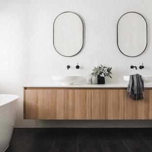 Ejemplo de cuarto de baño principal, contemporáneo, con armarios con paneles lisos, puertas de armario de madera clara, bañera exenta, baldosas y/o azulejos blancos, baldosas y/o azulejos en mosaico, paredes blancas, lavabo sobreencimera, suelo negro y encimeras blancas