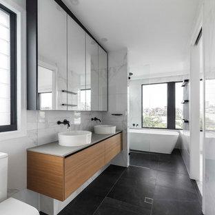 Immagine di una stanza da bagno padronale contemporanea con ante in legno chiaro, vasca freestanding, zona vasca/doccia separata, piastrelle bianche, pareti bianche, pavimento con piastrelle in ceramica, pavimento grigio e top grigio