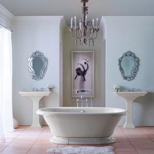 Foto de cuarto de baño principal, romántico, grande, con bañera exenta, ducha empotrada, paredes blancas, suelo de baldosas de cerámica, lavabo con pedestal y suelo rosa