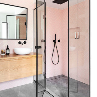На фото: главная ванная комната в современном стиле с душем в нише, розовой плиткой, керамической плиткой, белыми стенами, столешницей из дерева, серым полом, душем с распашными дверями, бежевой столешницей, тумбой под две раковины, подвесной тумбой, плоскими фасадами, светлыми деревянными фасадами и настольной раковиной с
