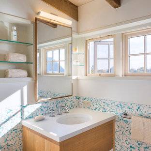 Inspiration for a beach style bathroom remodel in New York with flat-panel cabinets, light wood cabinets, multicolored walls, an undermount sink and white countertops