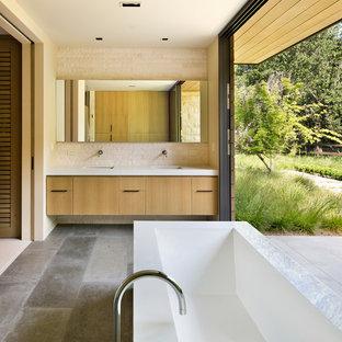 Modern inredning av ett badrum, med ett undermonterad handfat, släta luckor, skåp i mellenmörkt trä, ett fristående badkar och beige kakel