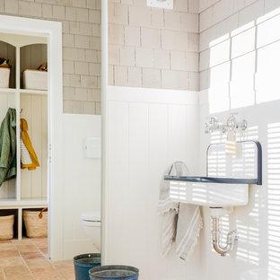 Foto di una stanza da bagno tradizionale con WC sospeso, piastrelle multicolore, pareti multicolore, pavimento in terracotta, lavabo sospeso e pavimento arancione