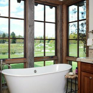 Foto de cuarto de baño principal, rústico, de tamaño medio, con puertas de armario de madera en tonos medios, bañera exenta, paredes blancas, armarios estilo shaker, suelo de baldosas de cerámica y encimera de granito