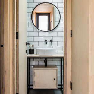 This is an example of a scandinavian bathroom in Oxfordshire with flat-panel cabinets, light wood cabinets, white tile, subway tile, white walls, concrete floors, a vessel sink, wood benchtops, grey floor and beige benchtops.