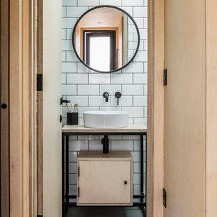 Foto di una stanza da bagno scandinava con ante lisce, ante in legno chiaro, piastrelle bianche, piastrelle diamantate, pareti bianche, pavimento in cemento, lavabo a bacinella, top in legno, pavimento grigio e top beige