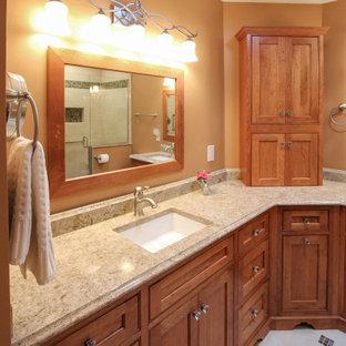 クリーブランドの中くらいのトラディショナルスタイルのおしゃれなマスターバスルーム (レイズドパネル扉のキャビネット、中間色木目調キャビネット、アルコーブ型シャワー、分離型トイレ、ベージュのタイル、セラミックタイル、オレンジの壁、磁器タイルの床、アンダーカウンター洗面器、クオーツストーンの洗面台、ベージュの床、開き戸のシャワー、ベージュのカウンター) の写真