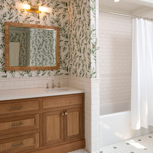 Inspiration for a mediterranean bathroom in Minneapolis with beaded cabinets, medium wood cabinets, an alcove bath, a one-piece toilet, white tiles, ceramic tiles, white walls, porcelain flooring, a submerged sink, engineered stone worktops, green floors, a hinged door, white worktops, a single sink, a built in vanity unit and wallpapered walls.