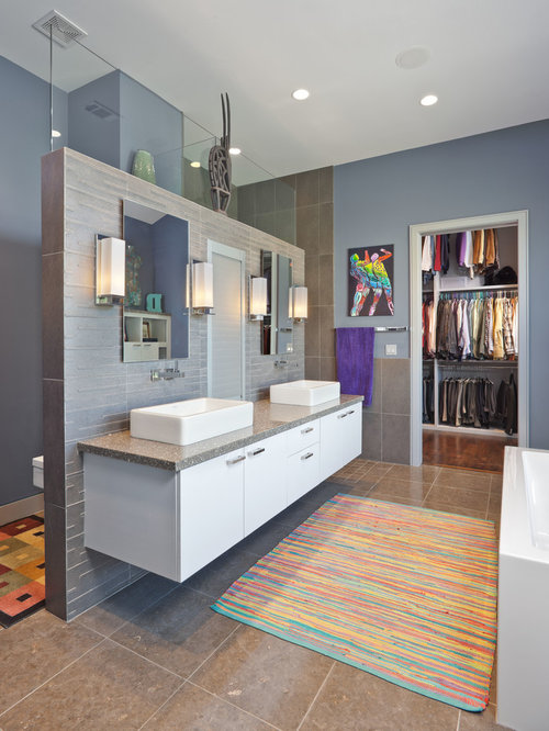 ... flat-panel cabinets, white cabinets, a freestanding tub and gray tile
