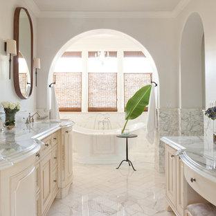 Ejemplo de cuarto de baño mediterráneo con lavabo bajoencimera, armarios con paneles con relieve, puertas de armario beige, bañera exenta y paredes blancas
