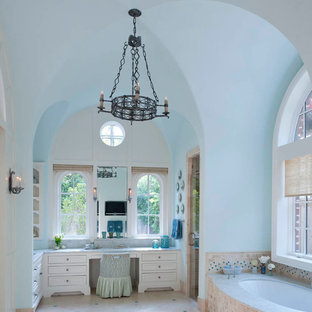 This is an example of a mediterranean bathroom in Dallas with white cabinets, a submerged bath, beige tiles and quartz worktops.