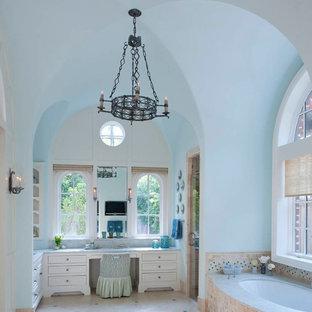 Foto di una stanza da bagno mediterranea con ante bianche, vasca sottopiano, piastrelle beige e top in quarzite