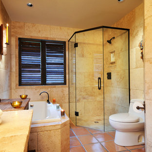 Design ideas for a large mediterranean ensuite bathroom in Other with a two-piece toilet, beige tiles, beige walls, terracotta flooring, wooden worktops, brown floors, a hinged door, a corner shower, stone tiles and a vessel sink.