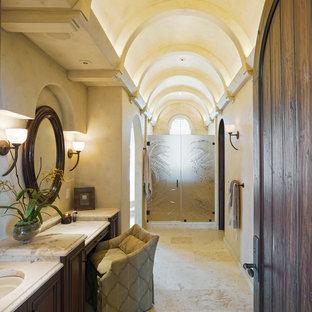 Ejemplo de cuarto de baño mediterráneo con lavabo bajoencimera, puertas de armario de madera en tonos medios, ducha empotrada, baldosas y/o azulejos beige y paredes beige
