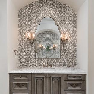 Ejemplo de cuarto de baño principal, mediterráneo, extra grande, con encimera de mármol, armarios con paneles empotrados, puertas de armario grises, baldosas y/o azulejos marrones, baldosas y/o azulejos blancos, paredes blancas, lavabo bajoencimera, suelo blanco y encimeras blancas