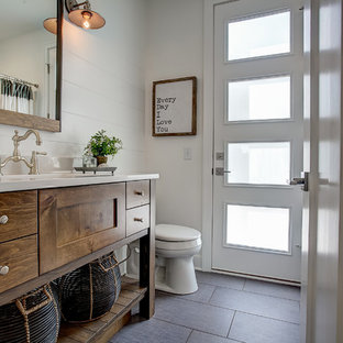 Design ideas for a mediterranean 3/4 bathroom in Grand Rapids with flat-panel cabinets, dark wood cabinets, white walls, an integrated sink and grey floor.