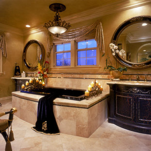 Mediterranean bathroom in Orange County with a submerged sink, dark wood cabinets, a built-in bath, beige tiles and travertine tiles.