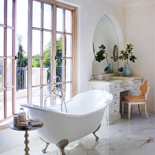 Inspiration for a huge mediterranean master marble floor and multicolored floor claw-foot bathtub remodel in Orange County with furniture-like cabinets, white cabinets, white walls and limestone countertops