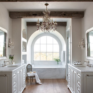 Mediterranean bathroom in Austin with a submerged sink, raised-panel cabinets, white cabinets, a submerged bath, white walls and medium hardwood flooring.