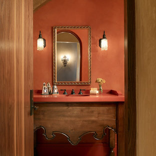 Inspiration for a mediterranean beige tile bathroom remodel in San Francisco with furniture-like cabinets, medium tone wood cabinets and orange walls