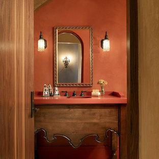 Immagine di una stanza da bagno mediterranea con consolle stile comò, ante in legno scuro, piastrelle beige e pareti arancioni