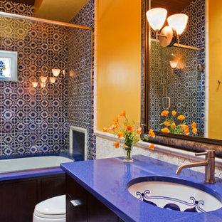 Ispirazione per una stanza da bagno per bambini mediterranea di medie dimensioni con lavabo sottopiano, ante lisce, ante in legno bruno, top in quarzo composito, vasca sottopiano, vasca/doccia, WC monopezzo, piastrelle blu, pareti gialle e top blu