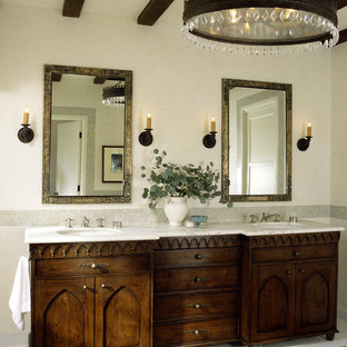 ロサンゼルスの地中海スタイルのおしゃれな浴室 (アンダーカウンター洗面器、落し込みパネル扉のキャビネット、濃色木目調キャビネット) の写真