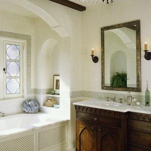 ロサンゼルスの地中海スタイルのおしゃれな浴室 (家具調キャビネット、濃色木目調キャビネット、アルコーブ型浴槽) の写真