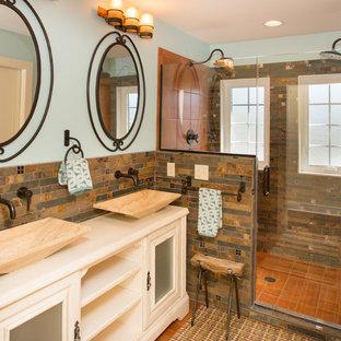 Свежая идея для дизайна: ванная комната среднего размера в средиземноморском стиле с стеклянными фасадами, белыми фасадами, душем в нише, бежевой плиткой, черной плиткой, коричневой плиткой, каменной плиткой, синими стенами, полом из керамической плитки, душевой кабиной, настольной раковиной, столешницей из искусственного камня, коричневым полом и душем с распашными дверями - отличное фото интерьера