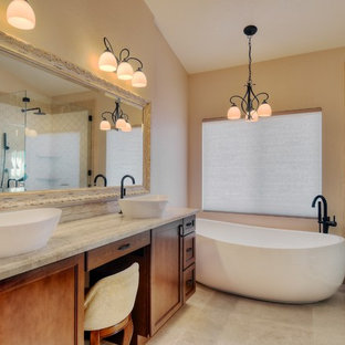 Photo of a medium sized mediterranean ensuite bathroom in San Diego with a vessel sink, raised-panel cabinets, dark wood cabinets, a freestanding bath, a corner shower, a two-piece toilet, beige tiles, stone tiles, beige walls and travertine flooring.
